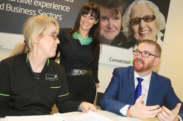 Minister pictured with staff members at Connected Health Belfast