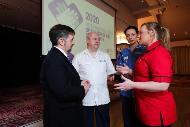 Health Minister Robin Swann is pictured with Student Nurse Craig Chambers, Staff Nurse Rebecca Stark (blue) and District Nursing Sister Ashleigh Pullins (red)